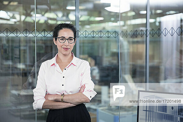Confident female entrepreneur leaning on glass wall at office