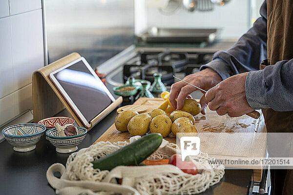 Senior man chopping potatoes on cutting board in kitchen