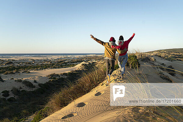 Couple with arm around running together on sand dune during sunset