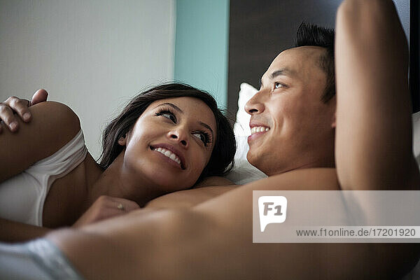 Girlfriend and boyfriend smiling while relaxing on bed at home