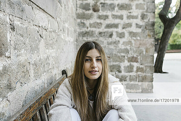 Young woman wearing jacket sitting on bench by wall