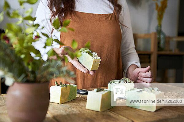 Frau zeigt ein Stück Seife in der Werkstatt Frau zeigt ein Stück Seife in der Werkstatt