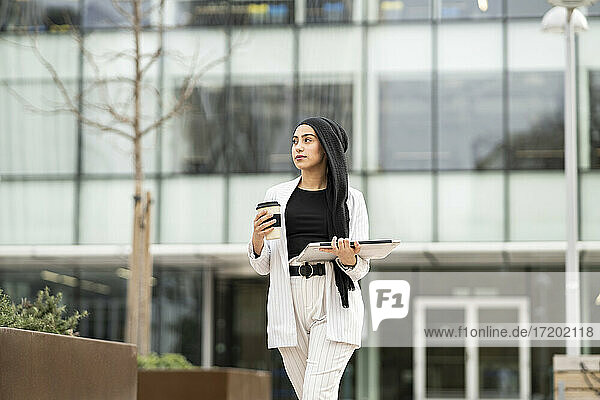 Young female entrepreneur with laptop and reusable cup walking outside office building