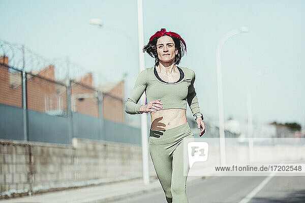 Woman with highlights running during sunny day