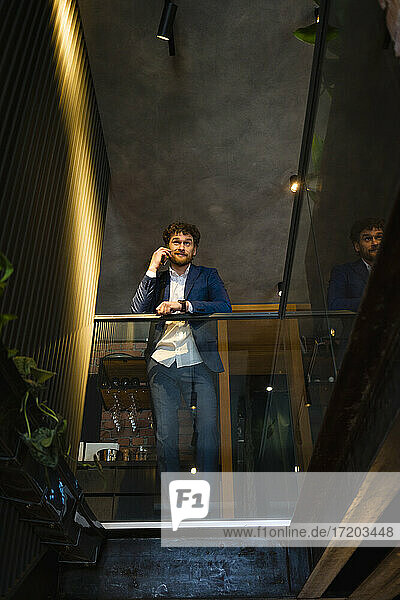 Businessman talking on mobile phone while leaning on railing at cafe