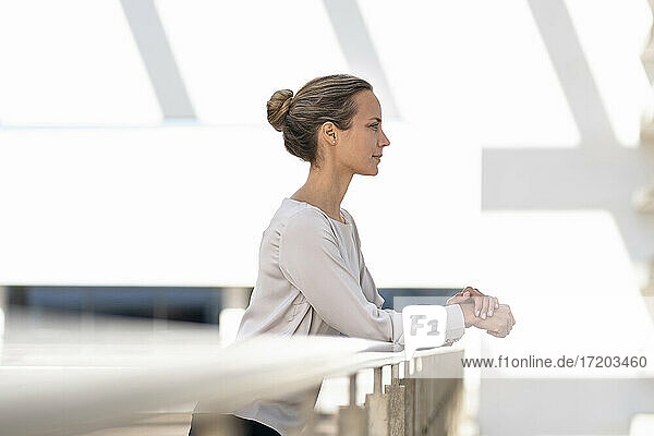 Contemplating businesswoman looking away while standing by railing at office terrace