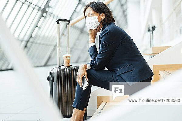 Female entrepreneur with hand on chin sitting on steps in corridor during pandemic