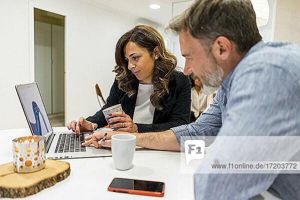 Männliche und weibliche Unternehmer planen ihre Strategie am Laptop  während sie in der Lobby ihres Büros sitzen