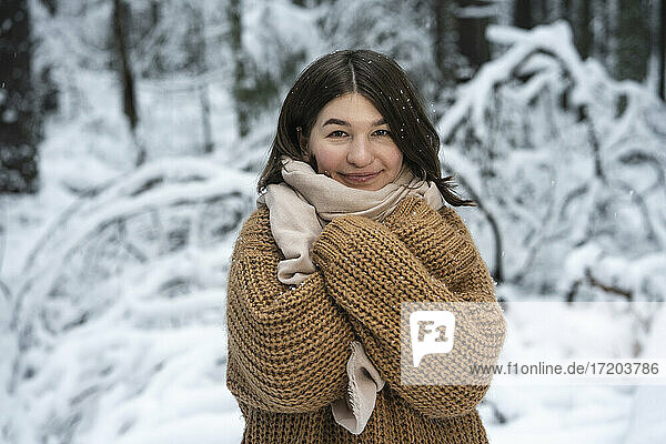 Young woman wearing sweater smiling while standing with arms crossed in forest