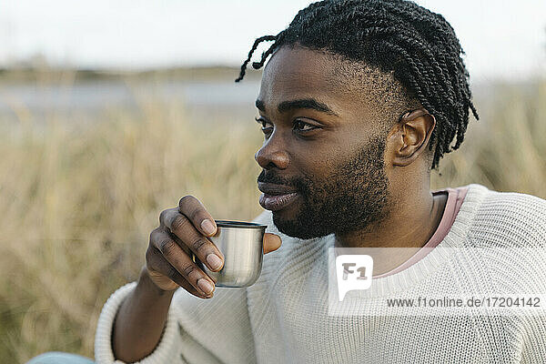 Smiling young man drinking tea while looking away