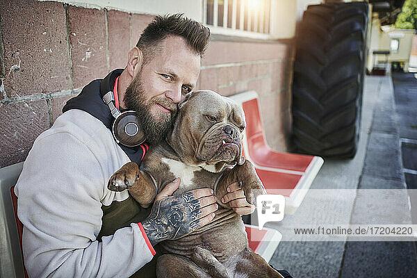 Männlicher Fitnesstrainer umarmt Bulldogge vor dem Fitnessstudio