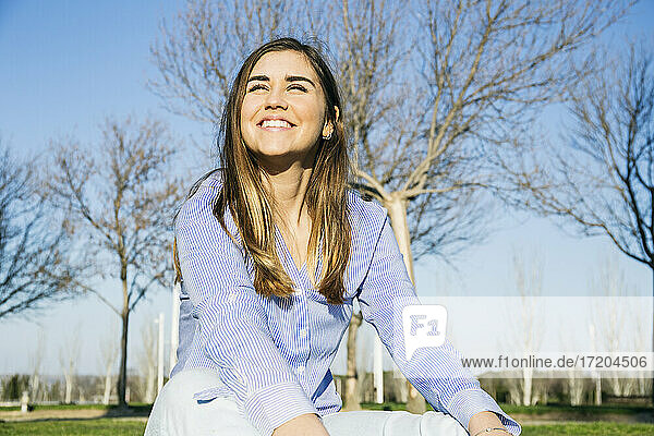 Happy woman smiling while sitting in park during sunny day