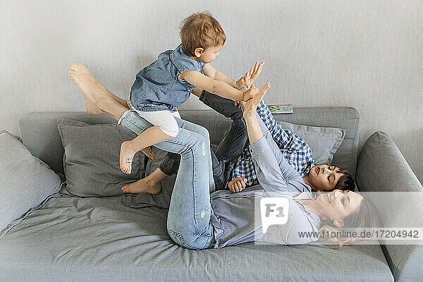 Mother lifting daughter by son on sofa at home