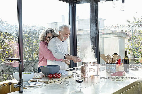 Smiling senior woman embracing man from behind in kitchen at home