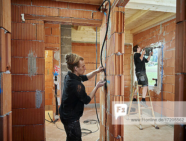Male electricians installing cables in brick wall while colleague working in background at construction site