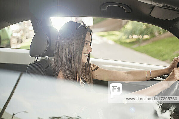 Smiling happy woman driving car