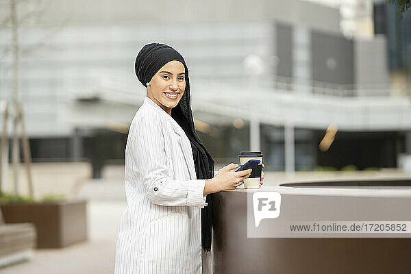 Smiling Arab woman standing at retaining wall with reusable cup and smart phone