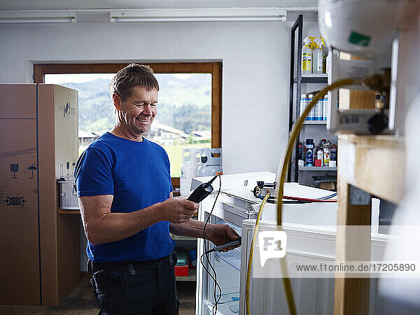 Smiling male electrician holding equipment while checking temperature at workshop