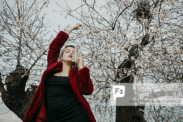 Young woman in red winter coat standing under blossoming almond tree during spring