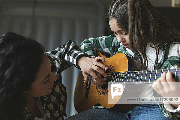 Mother teaching little daughter how to play acoustic guitar