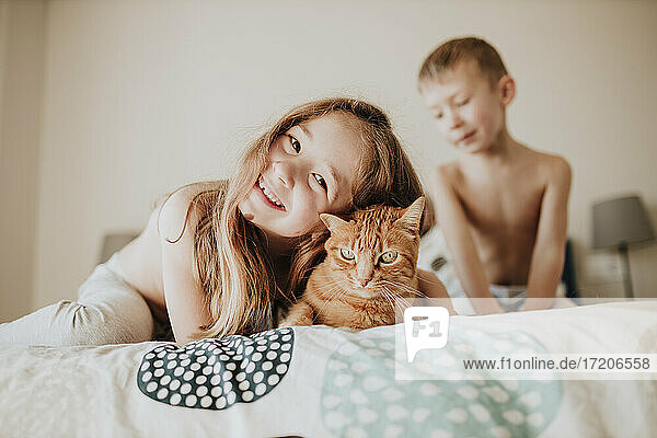 Smiling girl leaning on cat while brother in background in bedroom at home