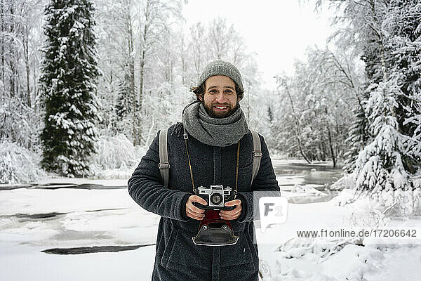 Young man with camera smiling while standing at snowy forest