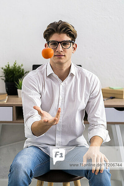 Young man throwing orange while sitting in living room