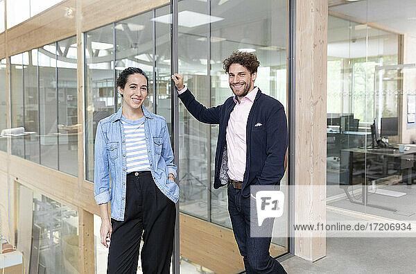 Lächelnde männliche und weibliche Unternehmer stehen vor einer Glaswand im Büro