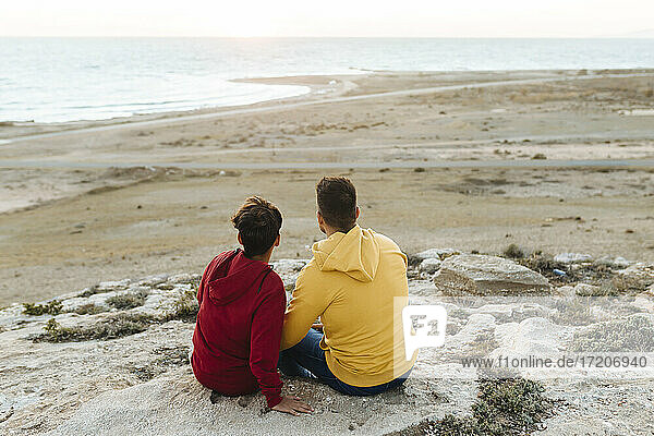 Father and son looking at view while sitting on rock