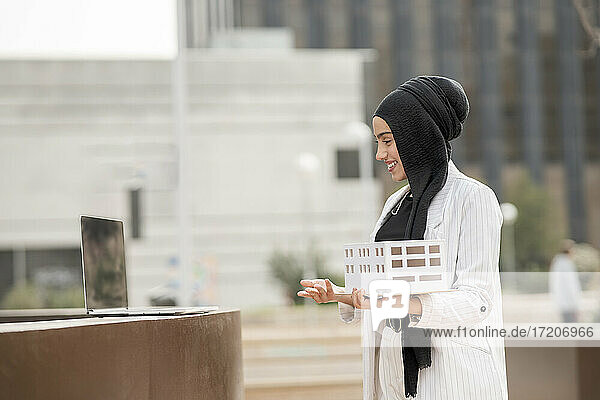 Young female architect holding architectural model during video call on laptop