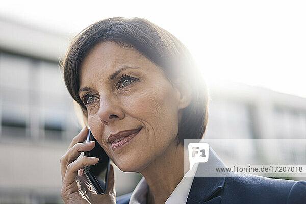 Reife Geschäftsfrau im Gespräch mit Smartphone im Freien