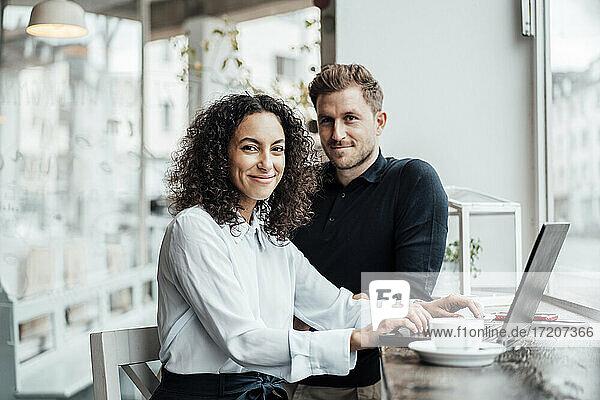Selbstbewusste Geschäftsfrau  die im Café neben einem Kollegen mit Laptop sitzt
