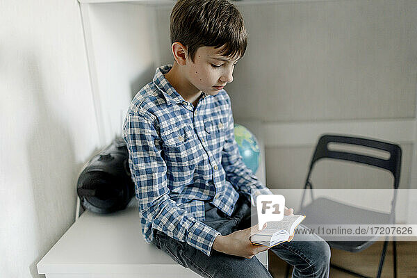 Boy reading dictionary while sitting on table at home