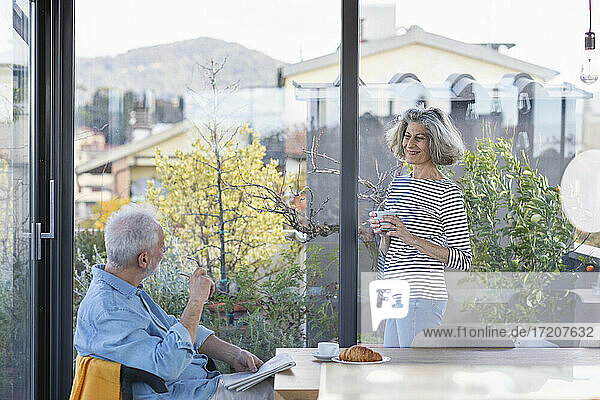 Smiling woman with coffee cup looking at man while standing by window at home