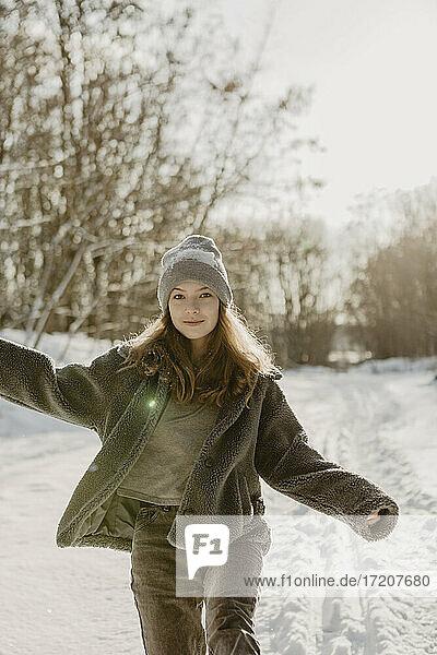 Portrait of beautiful teenage girl walking through snow toward camera