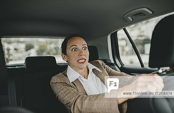 Scared businesswoman in back seat of car