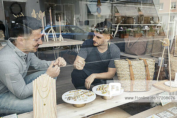 Customer with male entrepreneur trying rings seen through glass of design studio