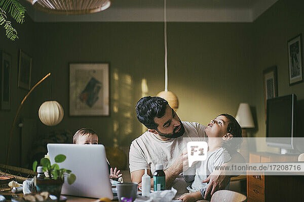 Father with children taking advice on video call through laptop at home during COVID-19