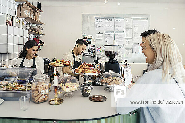 Smiling customers looking at male and female owners at delicatessen store