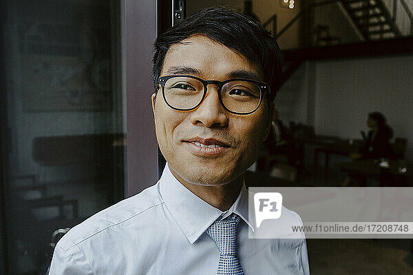 Happy male entrepreneur looking away in office