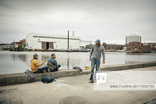 Man standing on skateboard while male friend photographing through smart phone sitting by canal