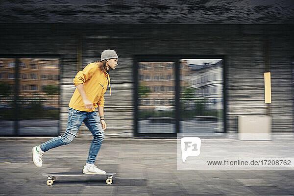 Mid adult man skating on footpath