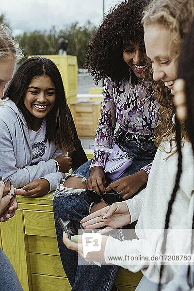 Teenage girl sharing smart phone with female friends