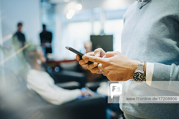 Midsection of businessman using smart phone at office
