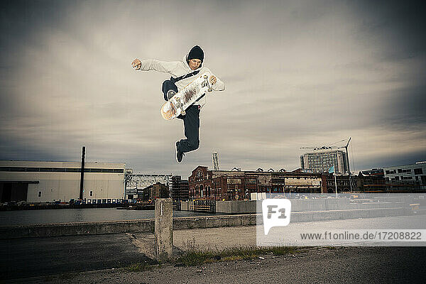 Male skateboarder jumping against sky at dusk