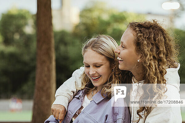 Female teenager friends laughing in park