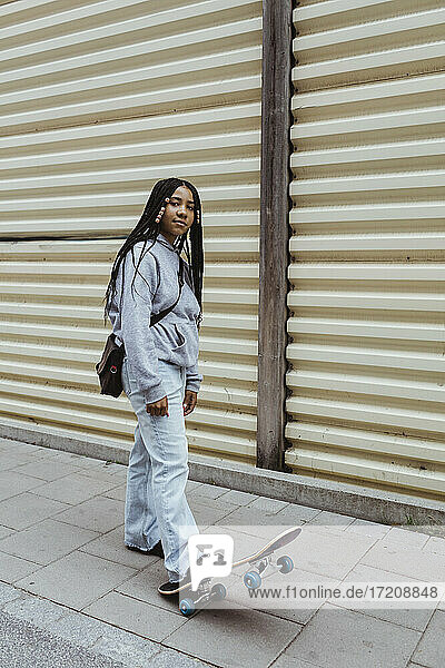 Teenage girl with skateboard on footpath by metal wall