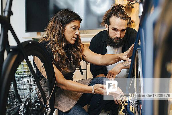 Female entrepreneur selling bicycle to male customer in repair shop