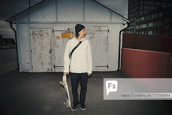 Man standing with skateboard against shed on street