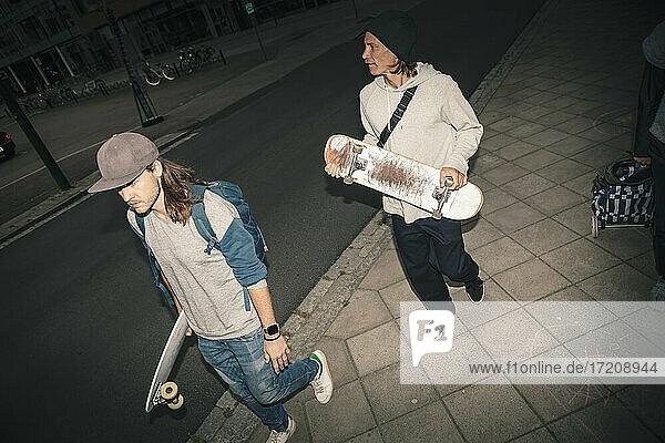 Male friends with skateboard walking on sidewalk